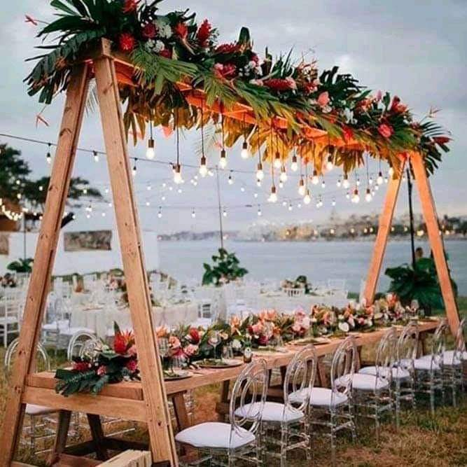 Wooden Canopy With Bistro Light Bulbs And Tropical Floral Garland